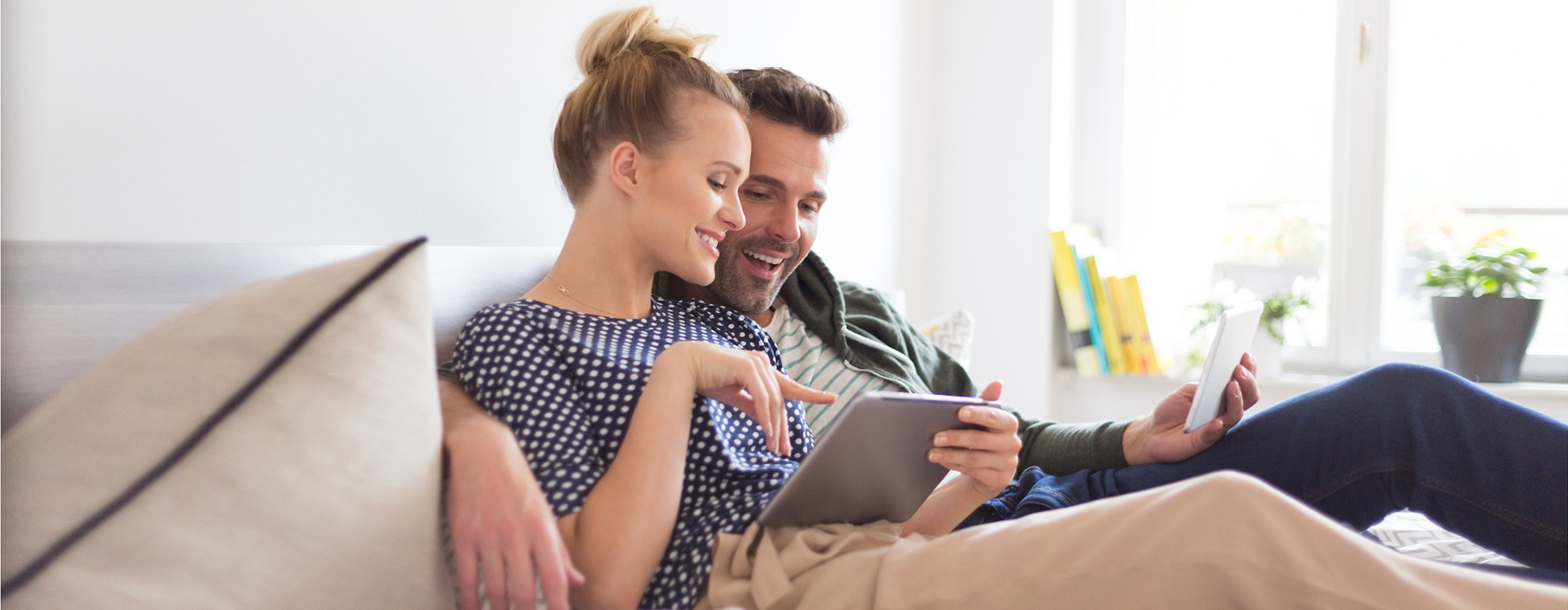 Man And Woman Sitting On Couch Using a Mobile Device
